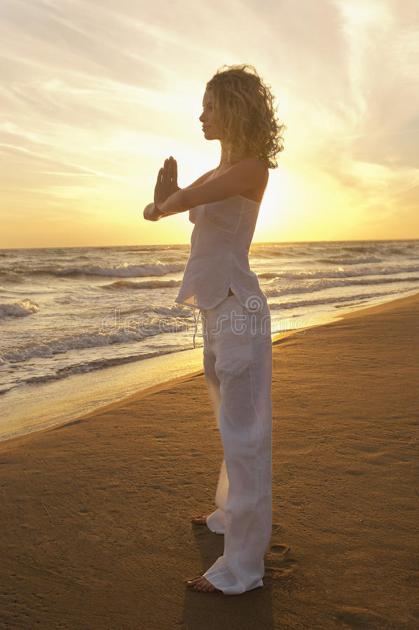 Femme avec du yoga de pratique étreint par mains à la plage images libres de droits