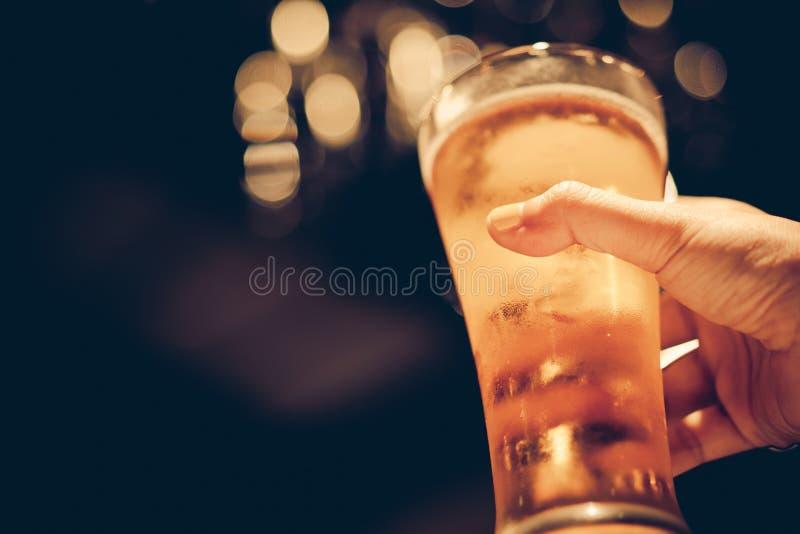 Femme avec jaune vernis à ongles tenant le verre de bière froide avec le beau bokeh photographie stock libre de droits