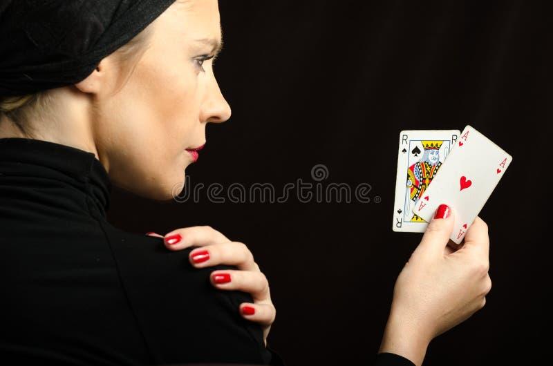 Femme avec jouer des cartes (paires de cric noir) photographie stock