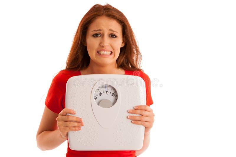 Femme avec l'échelle peu satisfaite de son poids faisant des gestes la tristesse et le W image libre de droits