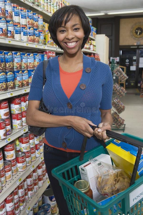 Femme avec l'épicerie dans le supermarché image stock