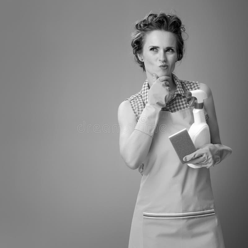 Femme avec l'éponge de cuisine et bouteille de détergent dessus photos stock