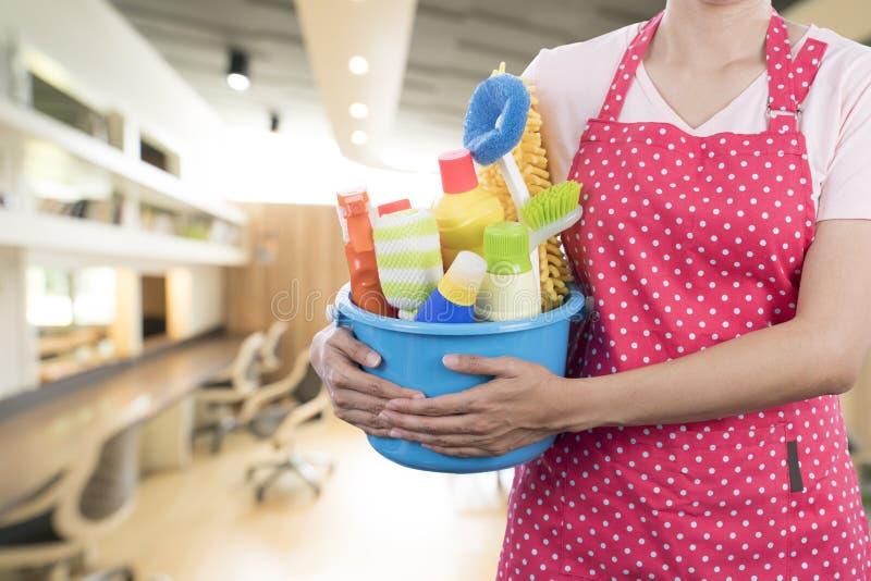 Femme avec l'équipement de nettoyage prêt à nettoyer la maison photographie stock libre de droits