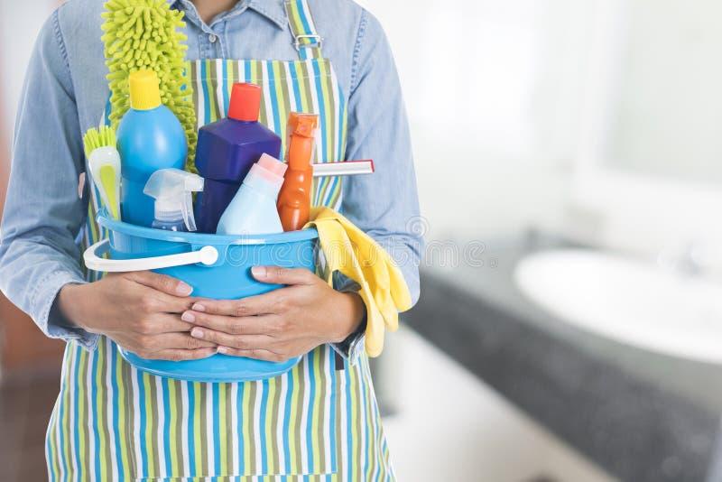 Femme avec l'équipement de nettoyage prêt à nettoyer la maison photographie stock