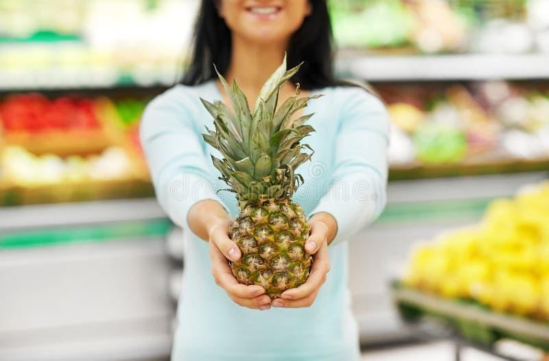 Femme avec l'ananas à l'épicerie photo stock