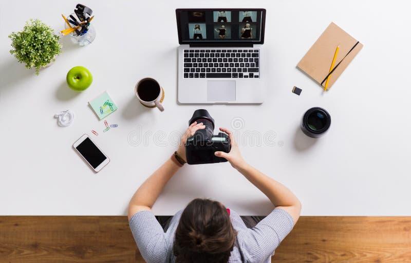 Femme avec l'appareil-photo et ordinateur portable à la table de bureau images stock
