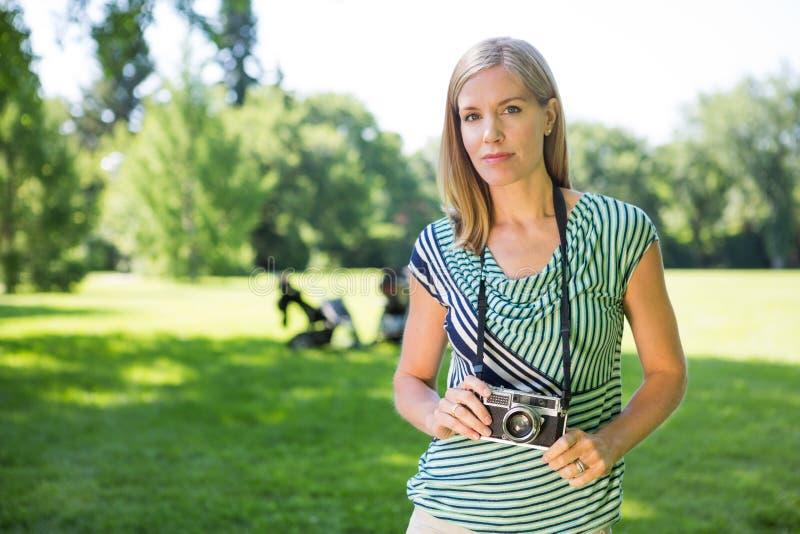 Femme avec l'appareil photo numérique en parc photo stock