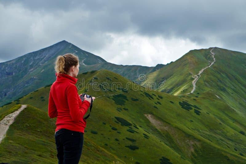 Femme avec l'appareil-photo sur un chemin de montagne photo libre de droits