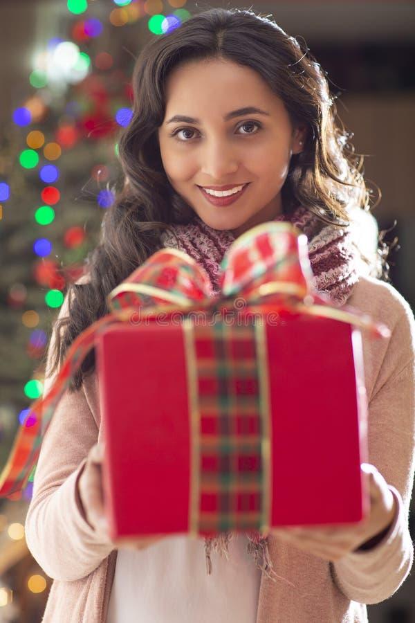 Femme avec l'arbre de cadeau et de Noël à l'arrière-plan image libre de droits