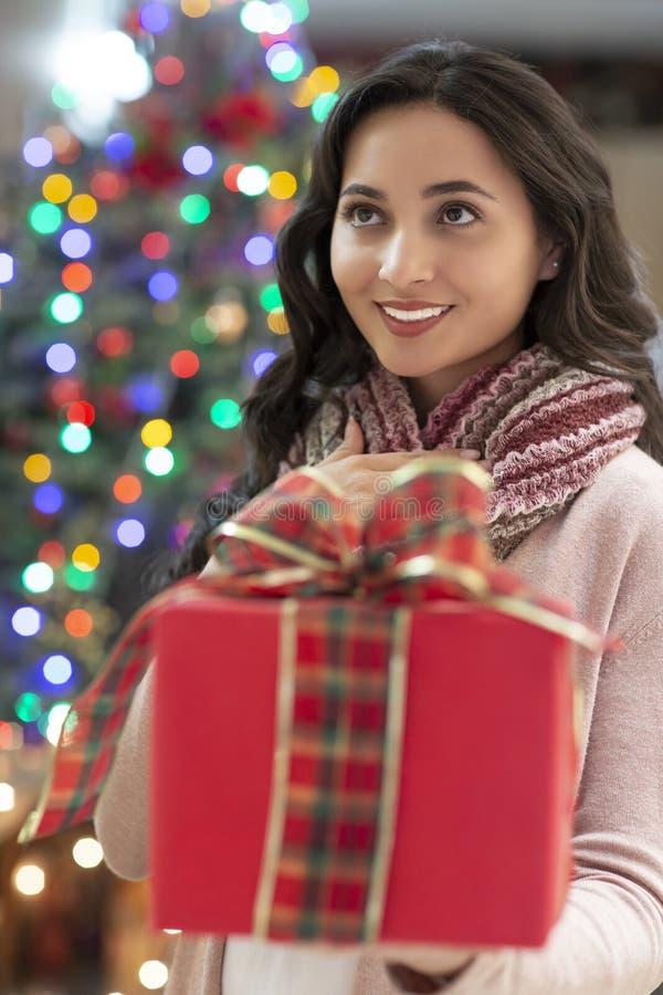 Femme avec l'arbre de cadeau et de Noël à l'arrière-plan photographie stock libre de droits