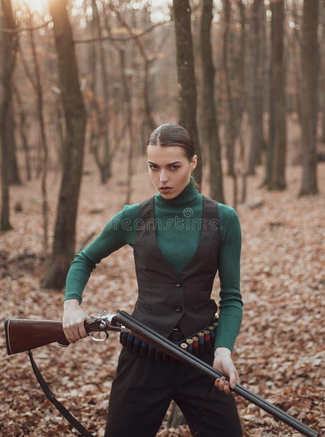 Femme avec l'arme Tir de cible Chasse r?ussie Sport de chasse Mode militaire Accomplissements des buts fille avec le fusil image stock