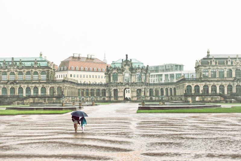 Femme avec l'enfant courant à partir de la pluie à Dresde photos stock
