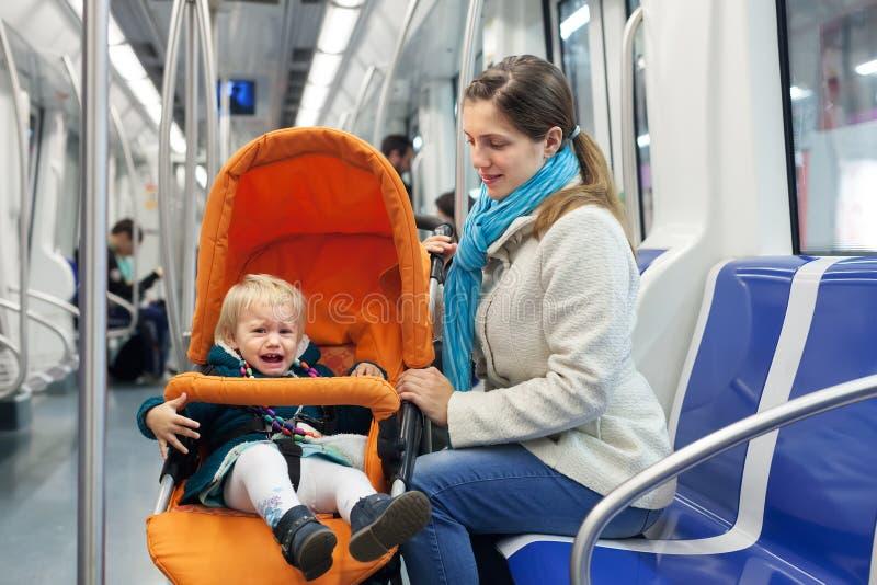 Femme avec l'enfant pleurant au souterrain photographie stock