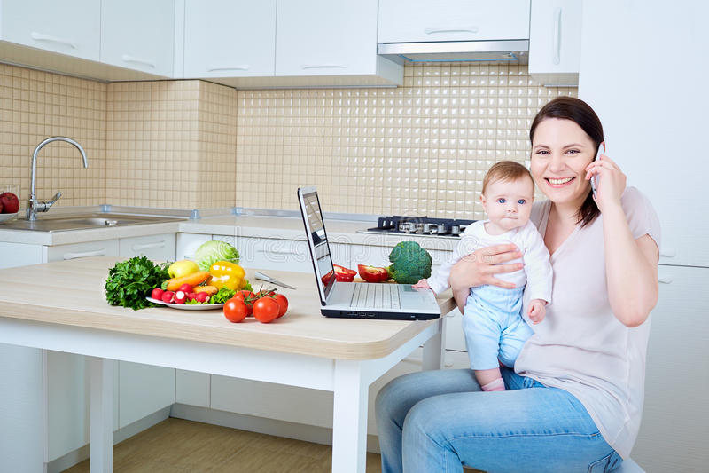 Femme avec l'enfant préparant la nourriture et parlant au téléphone F heureux photographie stock libre de droits