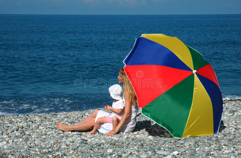 Femme avec l'enfant sous le parapluie sur la côte photos libres de droits