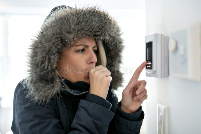 Femme avec l'habillement chaud sentant le froid à l'intérieur de la Chambre photos libres de droits