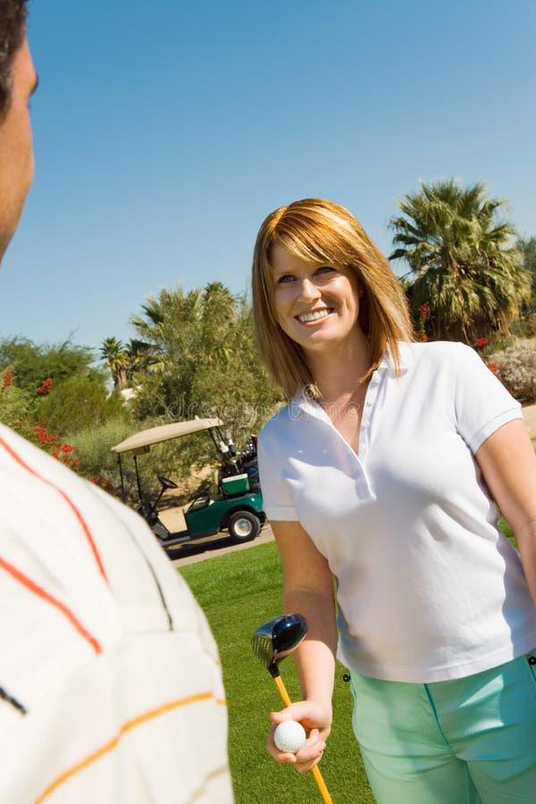 Femme avec l'homme au terrain de golf images stock