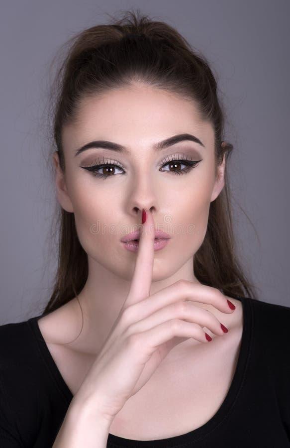 Femme avec l'index sur ses lèvres image libre de droits
