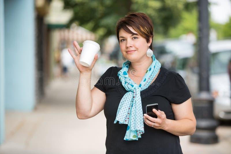 Femme avec l'ondulation de tasse de portable et de café photo stock