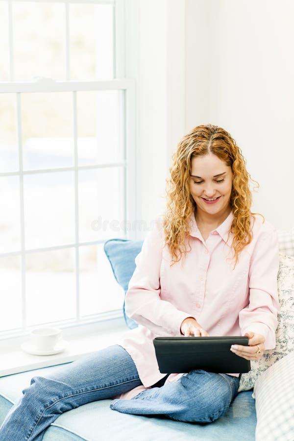 Femme avec l'ordinateur de tablette à la maison image stock