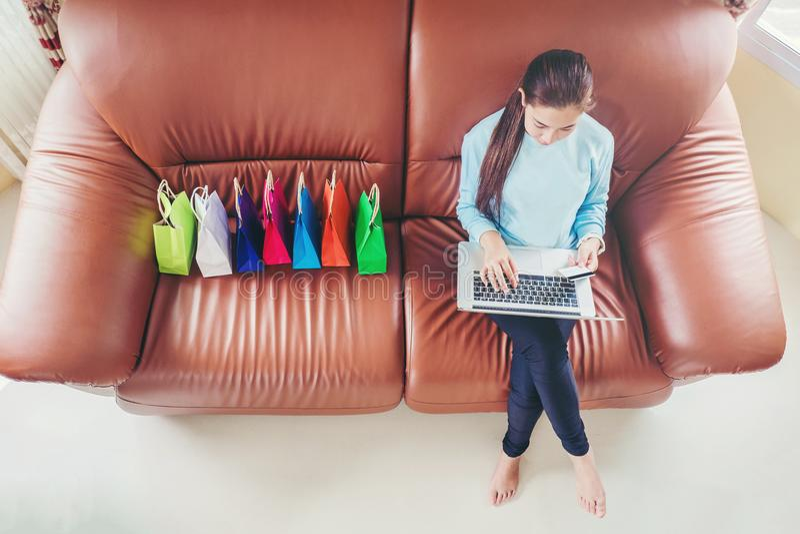 Femme avec l'ordinateur portable faisant des emplettes en ligne avec la carte de débit sur le sofa dans le hom photos libres de droits