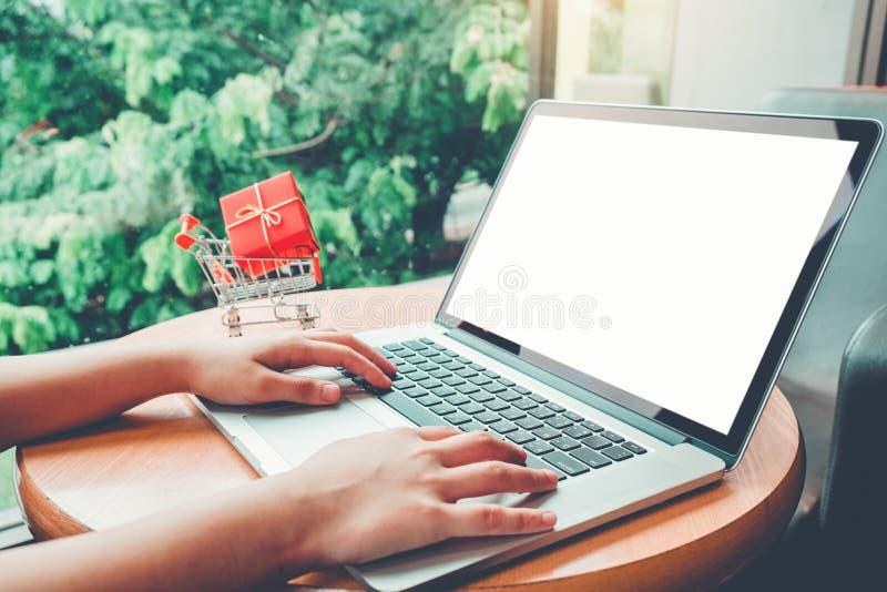 Femme avec l'ordinateur portable faisant des emplettes en ligne avec la carte de d?bit en caf? images stock