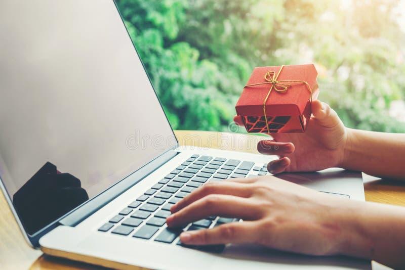 Femme avec l'ordinateur portable faisant des emplettes en ligne avec la carte de d?bit en caf? photo stock
