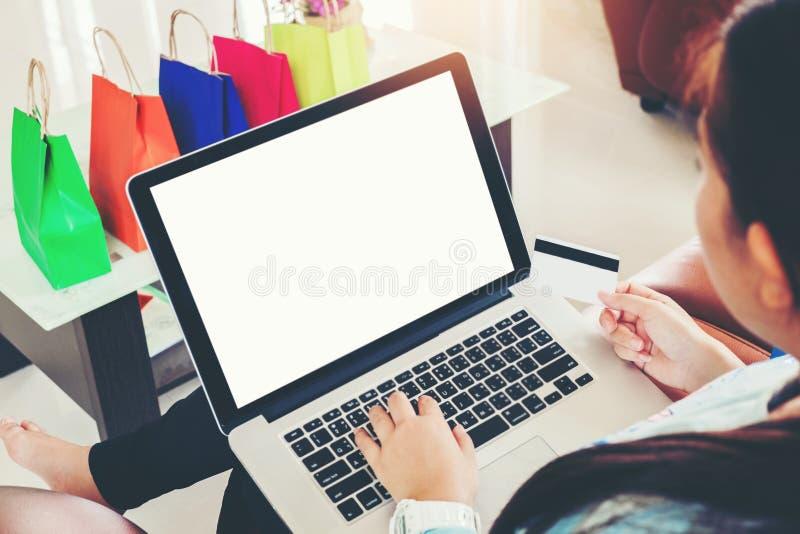 Femme avec l'ordinateur portable faisant des emplettes en ligne avec la carte de d?bit sur le sofa dans la maison images libres de droits