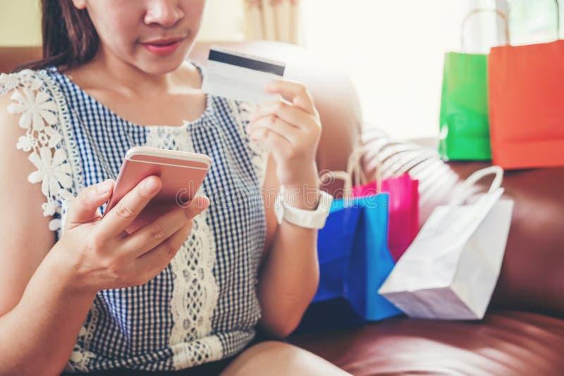 Femme avec l'ordinateur portable faisant des emplettes en ligne avec la carte de d?bit sur le sofa dans la maison photo stock