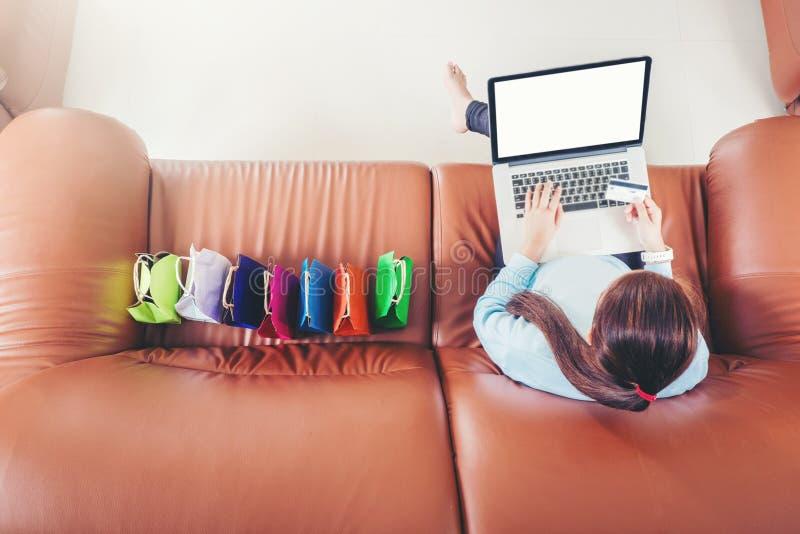 Femme avec l'ordinateur portable faisant des emplettes en ligne avec la carte de d?bit sur le sofa dans la maison photographie stock libre de droits