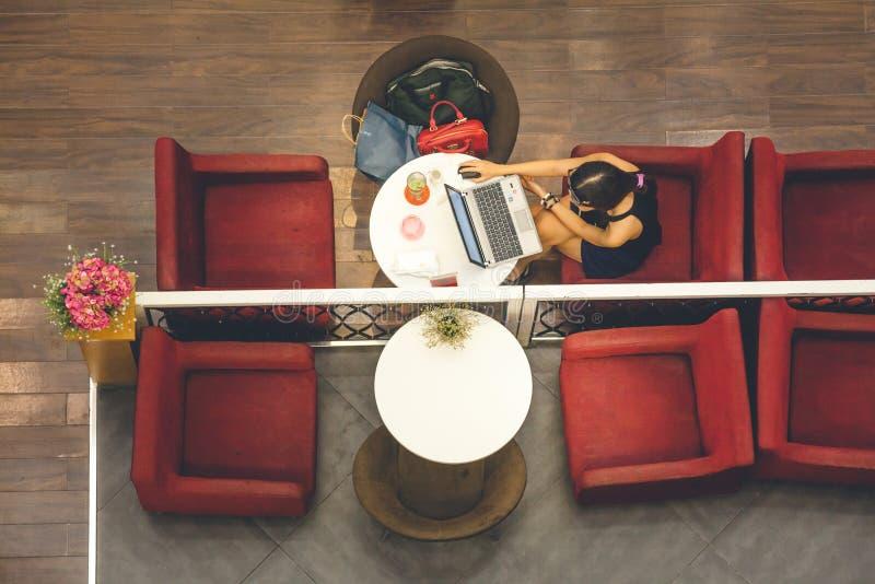 Femme avec l'ordinateur portable se reposant sur les tables d'une barre, vue courbe photo stock