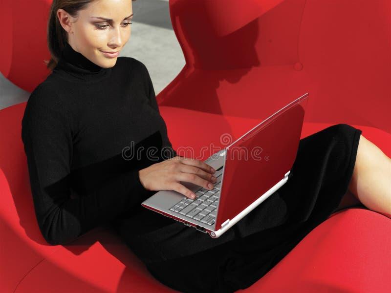 Femme avec l'ordinateur portable sur le sofa a photos libres de droits