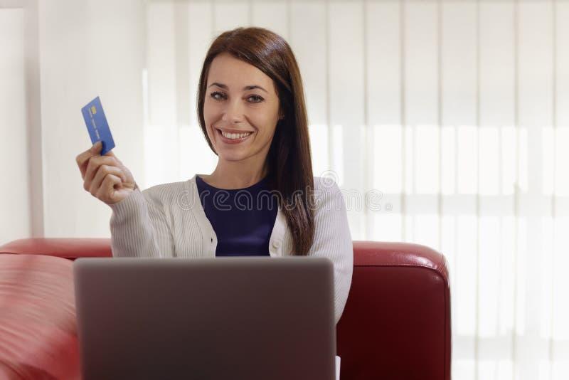 Femme avec l'ordinateur portatif et les achats par la carte de crédit photographie stock libre de droits
