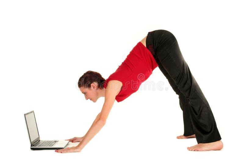 Femme avec l'ordinateur portatif faisant le yoga image libre de droits