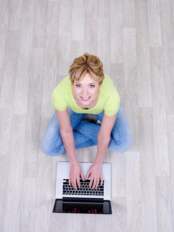 Femme avec l'ordinateur portatif sur l'étage image libre de droits
