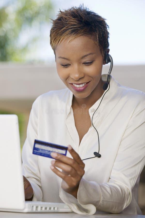 Femme avec l'ordinateur portatif sur le patio utilisant par la carte de crédit photo stock