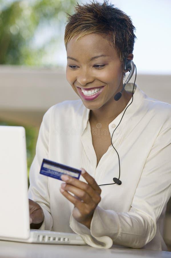 Femme avec l'ordinateur portatif sur le patio utilisant par la carte de crédit photos stock