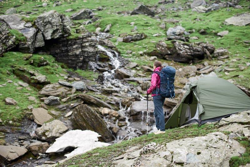Femme avec la belle vue du courant de montagne en montagnes de Fagaras photographie stock