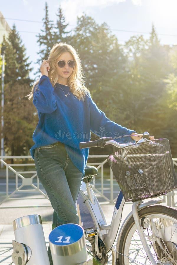Femme avec la bicyclette à la station de location photo stock