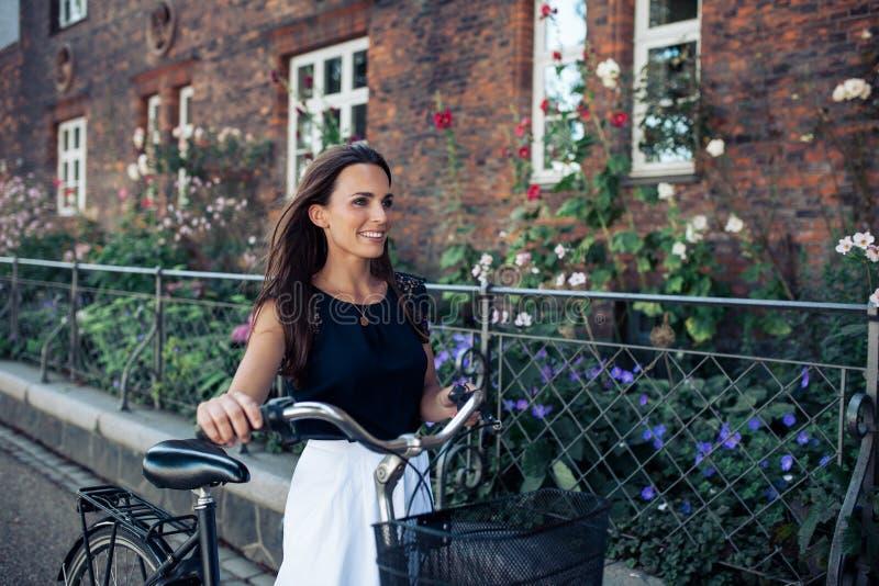 Femme avec la bicyclette descendant la rue photographie stock
