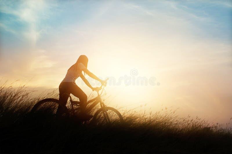 Femme avec la bicyclette sur une route rurale avec le fond de coucher du soleil d'herbe photo stock