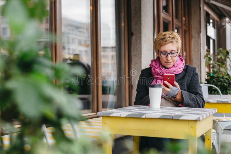 Femme avec la boisson et le smartphone photographie stock