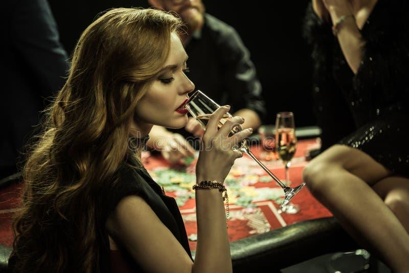 Femme avec la boisson jouant le tisonnier dans le casino images stock
