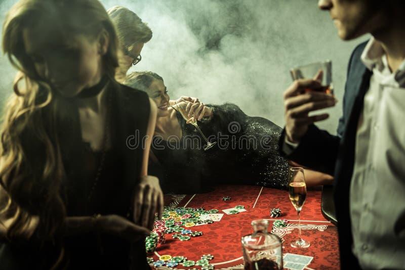 Femme avec la boisson se trouvant sur la table de tisonnier pendant le jeu dans le casino image libre de droits