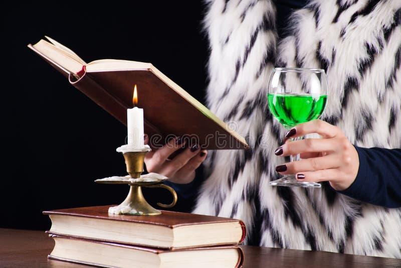 Femme avec la boisson verte d'absinthe dans le livre en verre de lecture image stock
