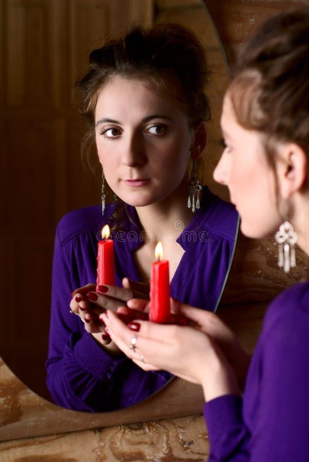 Femme avec la bougie devant un miroir. photo stock
