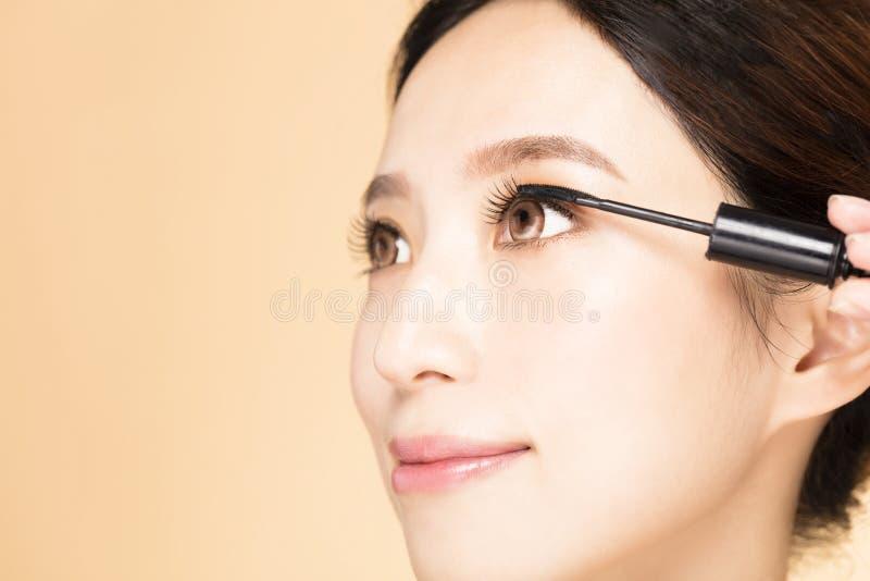 Femme avec la brosse de maquillage appliquant le mascara noir sur des cils images libres de droits