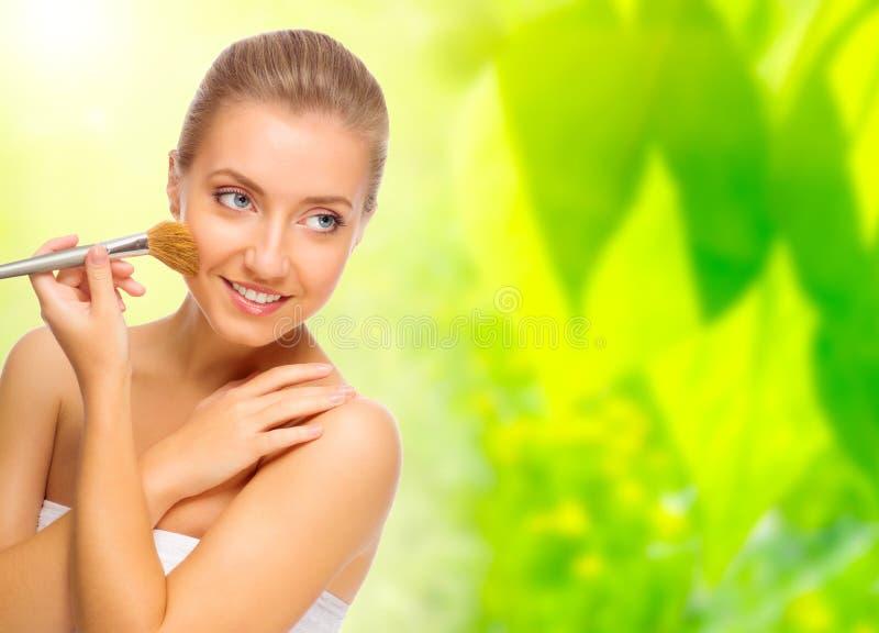 Femme avec la brosse de maquillage sur le fond floral image stock