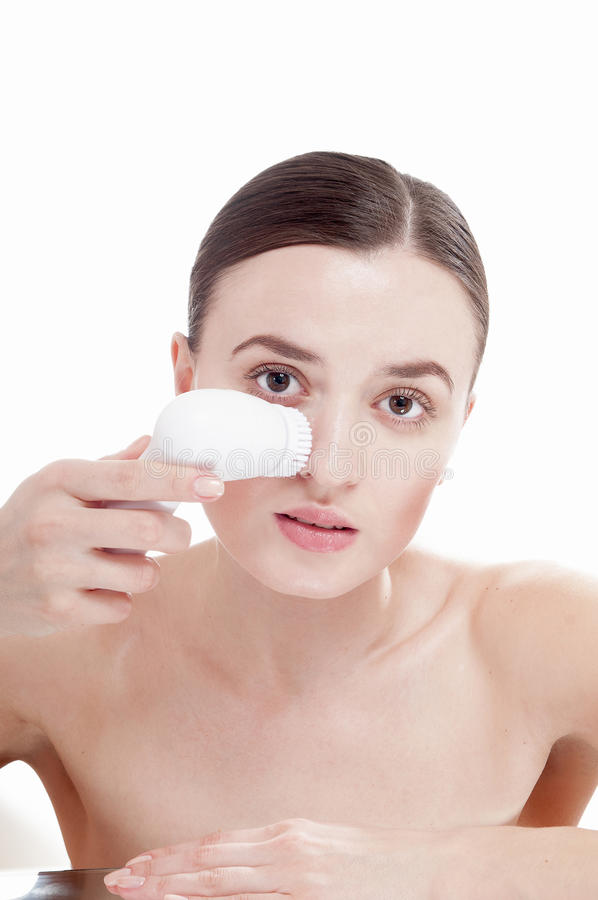 Femme avec la brosse pour le massage facial profondément de nettoyage. photo stock
