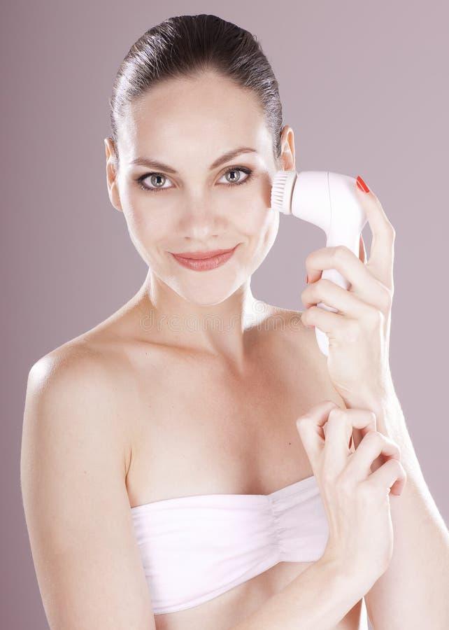 Femme avec la brosse pour le massage facial profondément de nettoyage photographie stock libre de droits